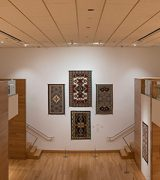 Long interior view form second floor balcony of Navajo rug exhibition showing rugs hanging on soft white walls with blond bamboo wood on floors and some wall panels.