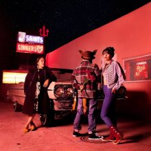 3 young people standing next to old cars bathed in red lighting with a neon sign in the dark background