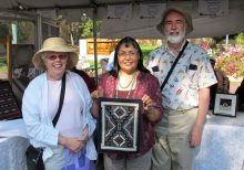 Mark and Julie Dalrymple posing for a picture with Navajo weaver Lynda Teller Pete as she holds one of her miniature weavings