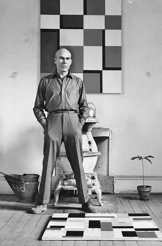 black and white photo of Leon Polk Smith standing with hands in pockets and feet spread slightly apart staring intently into the camera in front of a geometric painting on the wall and another on the floor.