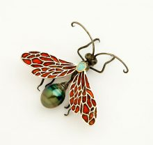Realistically executed jewelry pin in the form of a wasp with plique a jour red enamel wings and a black pearl as the adbomen. Metal is oxidized 14K gold. Made by Liz Wallace