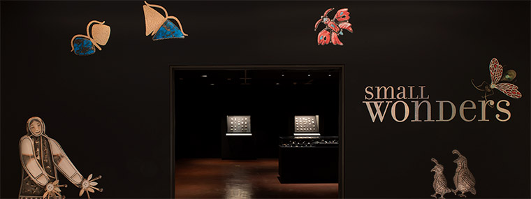 Entrance to the Small Wonders exhibition with images of jewelry of butterflies, quail, Inuit dancer and wasp on a black background