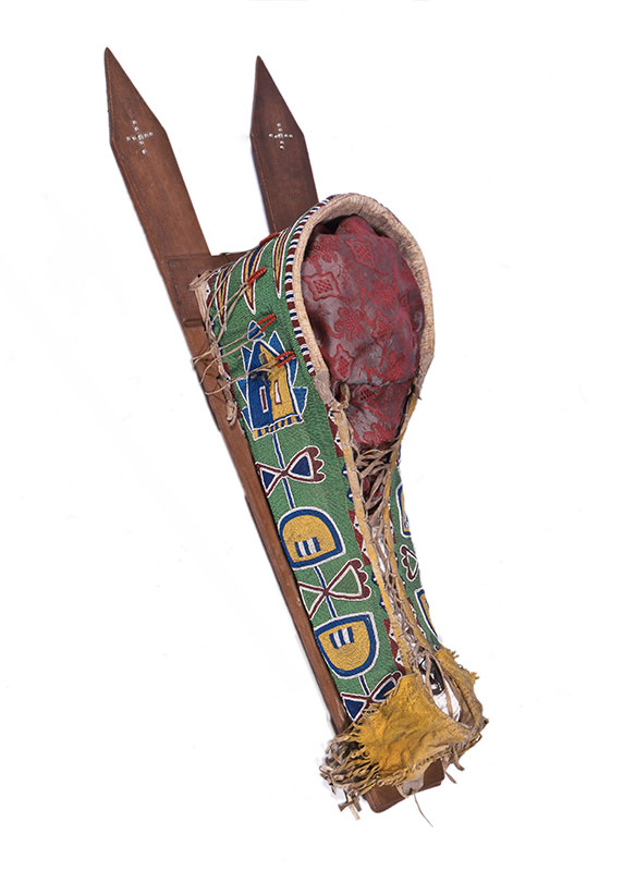Cradleboard from the Kiowa tribe, circa, 1890, with beadwork over leather and wooden flat boards on back