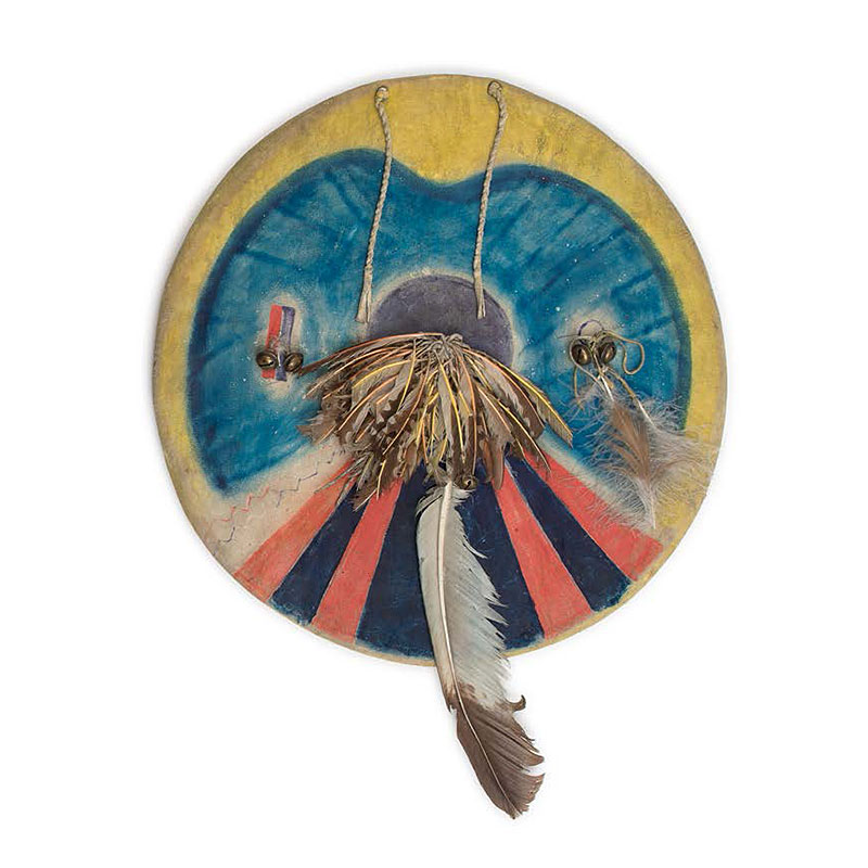 painted hide shield from the Comanche tribe, circa 1880 with a yellow border, blue center and black and red radiating stripes from center to bottom edge.