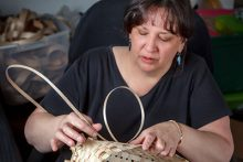 Native American basket weaver Kelly Church wearing a black shirt in the process weaving a basket