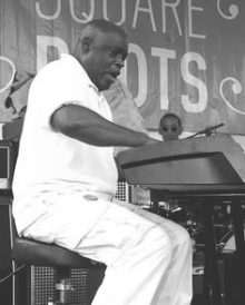 Doc Jones singing and playing the piano at a performance