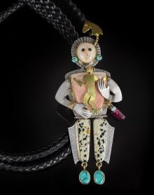 Native American bolo by Victoria Adams showing a figure in silver, gold and stones carrying a smaller figure in gold