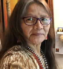 Navajo weaver Marilou Schultz wearing glasses and a gold colored velvet shirt smiling