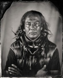 old-fashioned style black and white manipulated photo with burnt edges of Native American man with long disheveled hair an oxygen mask around his neck wearing short sleeves and a puffy vest.