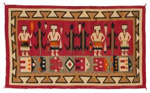 Handwoven Navajo weaving of multiple Ye'iibicheii with lizards in between all standing above house forms on a brown ground