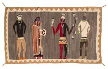 Handwoven Navajo weaving of 4 Ye'iibicheii in different garb standing in front of a heathered brown-cream striated background