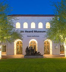 evening with golden lights wrapped around trees surrounding a green space with a Spanish Mission style facade building in the background with an arched colonnade running around the outside