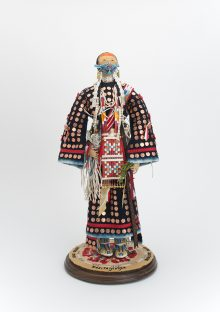 soft sculpture doll by Juanita Growing Thunder of a Native woman in traditional plains dress wearing a mask