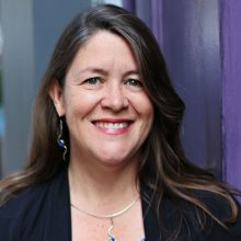 Author Traci Sorell smiling with long brown hair and wearing a dark jacket and long silver earrings with a matching necklace