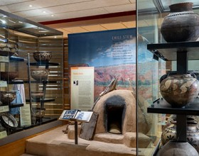 Section of the HOME exhibition showing Pueblo pottery and a traditional beehive bread oven made from clay