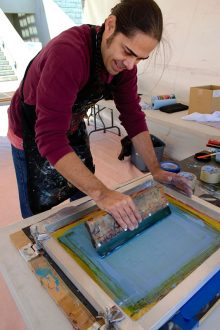 Native American printmaker Jake Meders wearing a long sleeved maroon shirt and black apron leaning over a table while pulling a squeegee across the printing area on a printing screen to push ink through