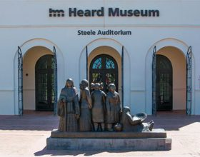 """Entrance to Steele Auditorium, a Spanish Revival style white stucco building with arched colonnade in front and the sculpture """"Intertribal Greeting"""" by Dough Hyde in the red brick paved courtyard in front featuring 5 Native women from the SW in traditional dress."""