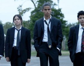 Scene from TV show Reservation Dogs showing 4 Native youth, 2 females and 2 males. dressed in black suits and white shirts like the characters in Reservation Dogs walking in a line through a parking lot.