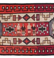 Navajo rug with red and tan background and complex geometric shapes surrounding a center area with Yei figures