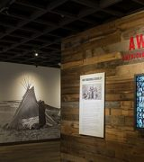 Entrance to exhibition Away from Home showing a dark wood board wall with a large TV showing animated school yearbook photos of American Indian boarding school students and a US map and wall photo of a person standing in front of a traditional teepee in the background