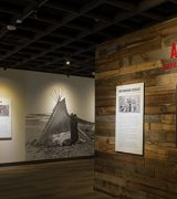 Entrance to the American Indian Boarding Schools exhibition showing a large monitor with rotating images of school yearbook pictures, didactic panels and a large map of the US showing Native land loss.