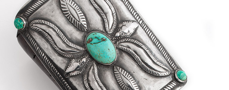 Detail of a silver ketoh (bow guard) decoration with an oval turquoise cabochon set in center and 4 round turquoise cabochons set at the 4 corners