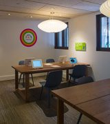 Its Your Turn children's activity space with wooden tables with iPads and hands on coloring activities, and books to read