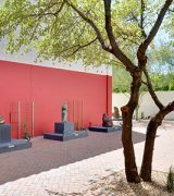 Sculpture garden with bronze and stone sculptures by American Indian artists ranged throughout a brick paved walled exterior space with one wall painted a bright red. Other walls are painted stucco white and various desert trees and foliage is arranged throughout.
