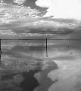 Black and white watery landscape with a young Navajo man standing in profile on the far right wearing a white shirt and traditional Navajo hair bun.