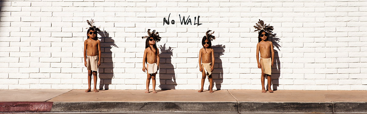 """4 American Indian children in breechclouts and feathers in their hair stand on the sidewalk in front of a white painted brick wall with the words, """"No Wall"""" painted in the middle."""