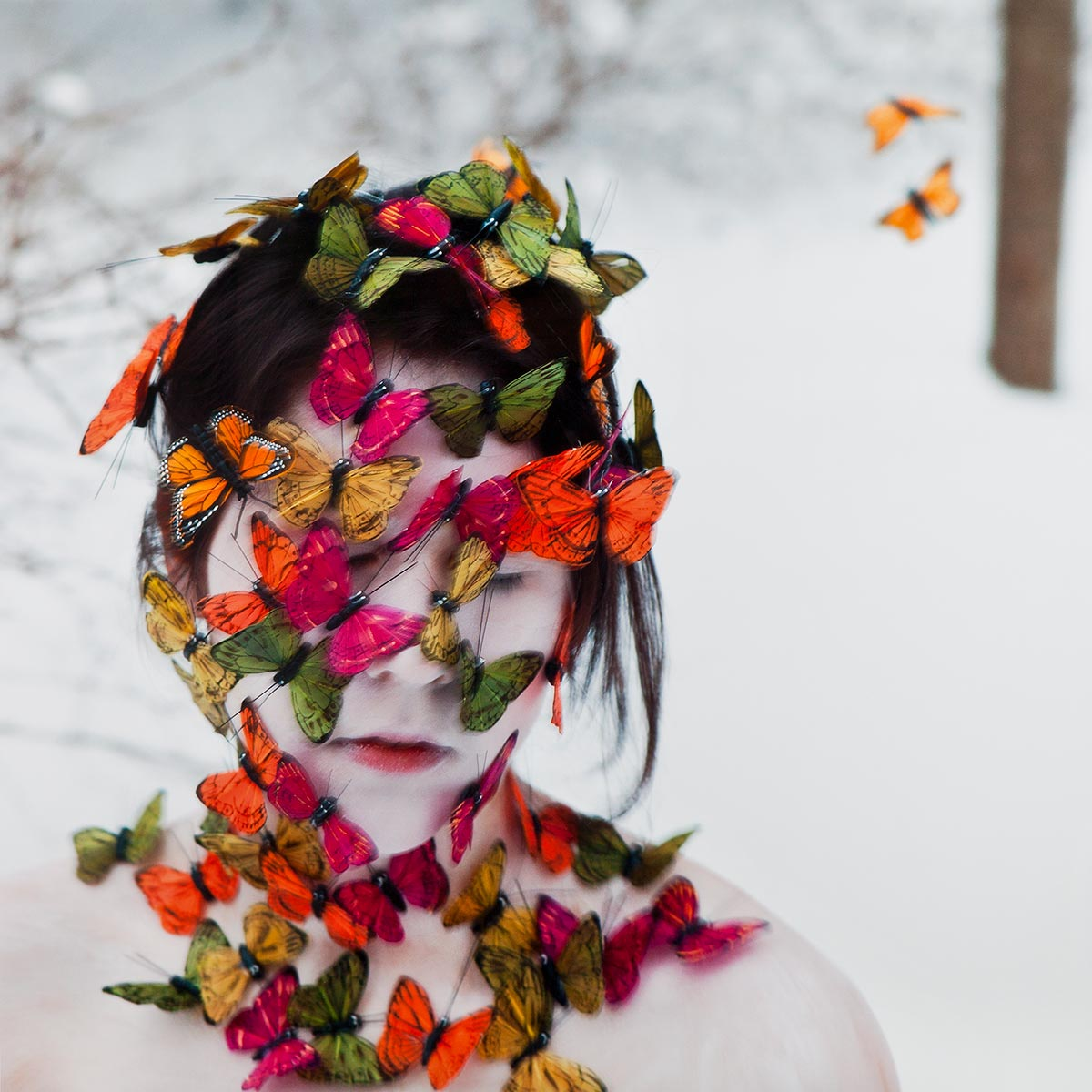 White snowy background with young woman in foreground covered in white makeup/powder shown from the shoulders up covered in green, fuschia, orange and yellow butterflies.