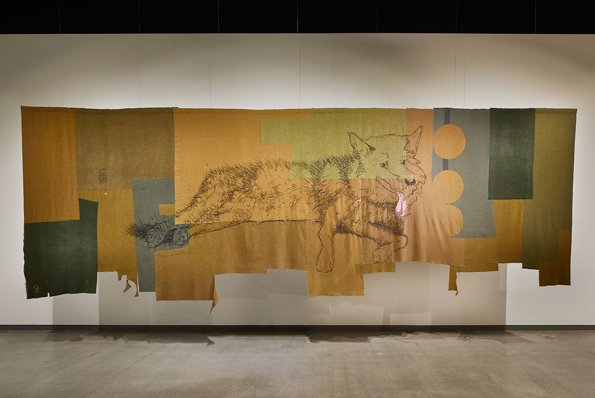 Mustard yellow, grey, brown and green fabric stitched together with a drawing of a female wolf reclining with her head up looking attentively, tongue lolling.