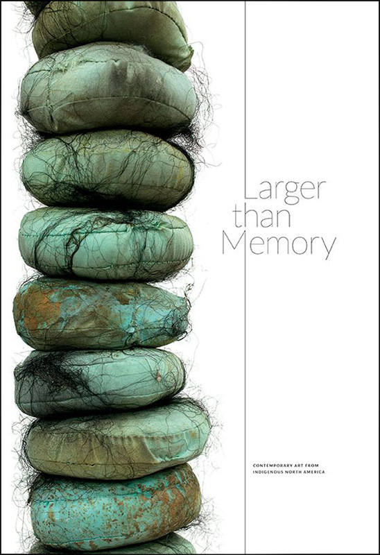 Larger Than Memory exhibition catalog cover with green turquoise and brown color fabric pill-shaped pillow forms with black hair-like webbing