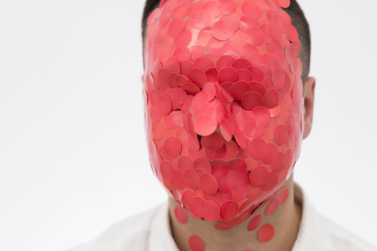 A man's face is completely covered with red paper dots.