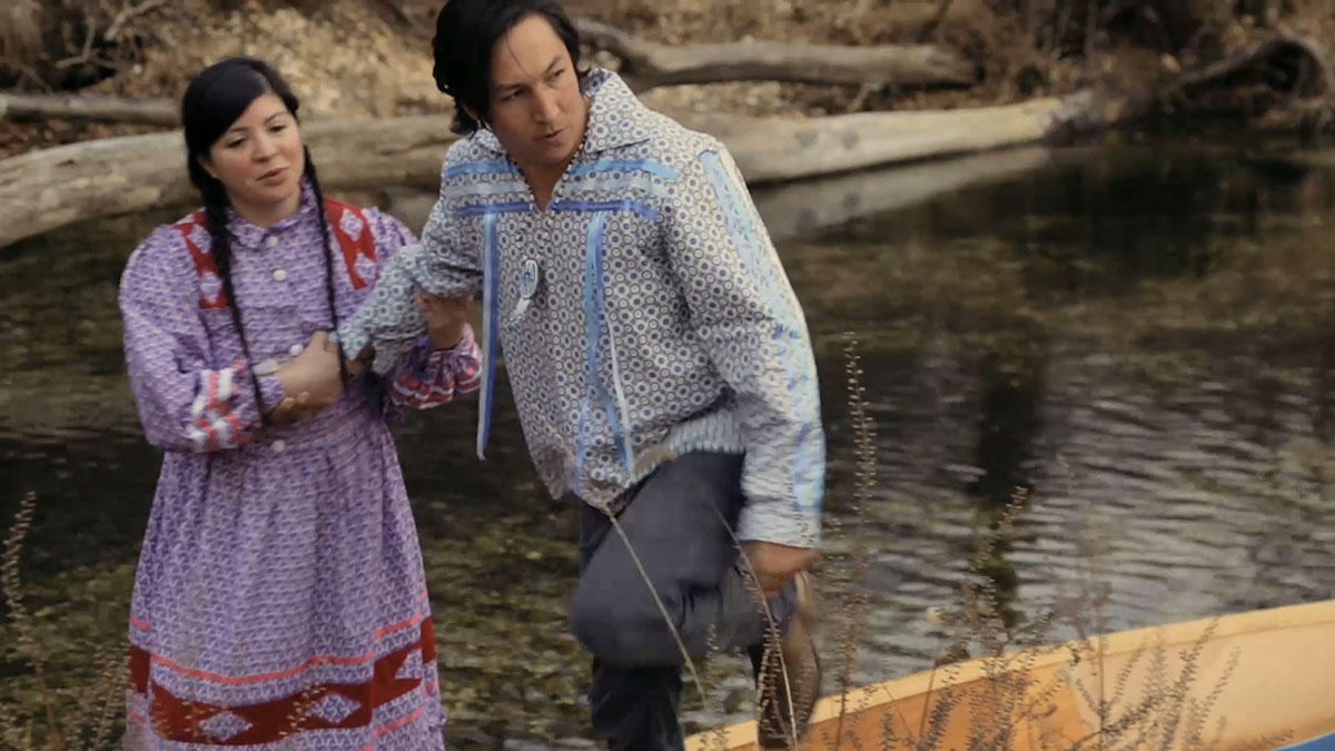 A young woman holds the arm of a young man by the side of a stream. Both are dressed in traditional clothing.