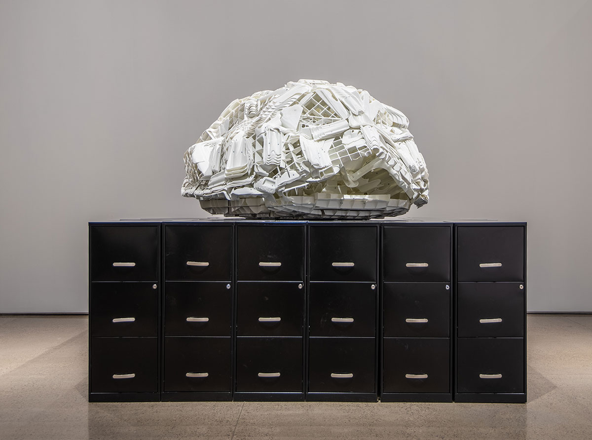 plinth of side by side black metal file cabinets on which sits melted white plastic lawn chairs forming the shape of a turtle shell