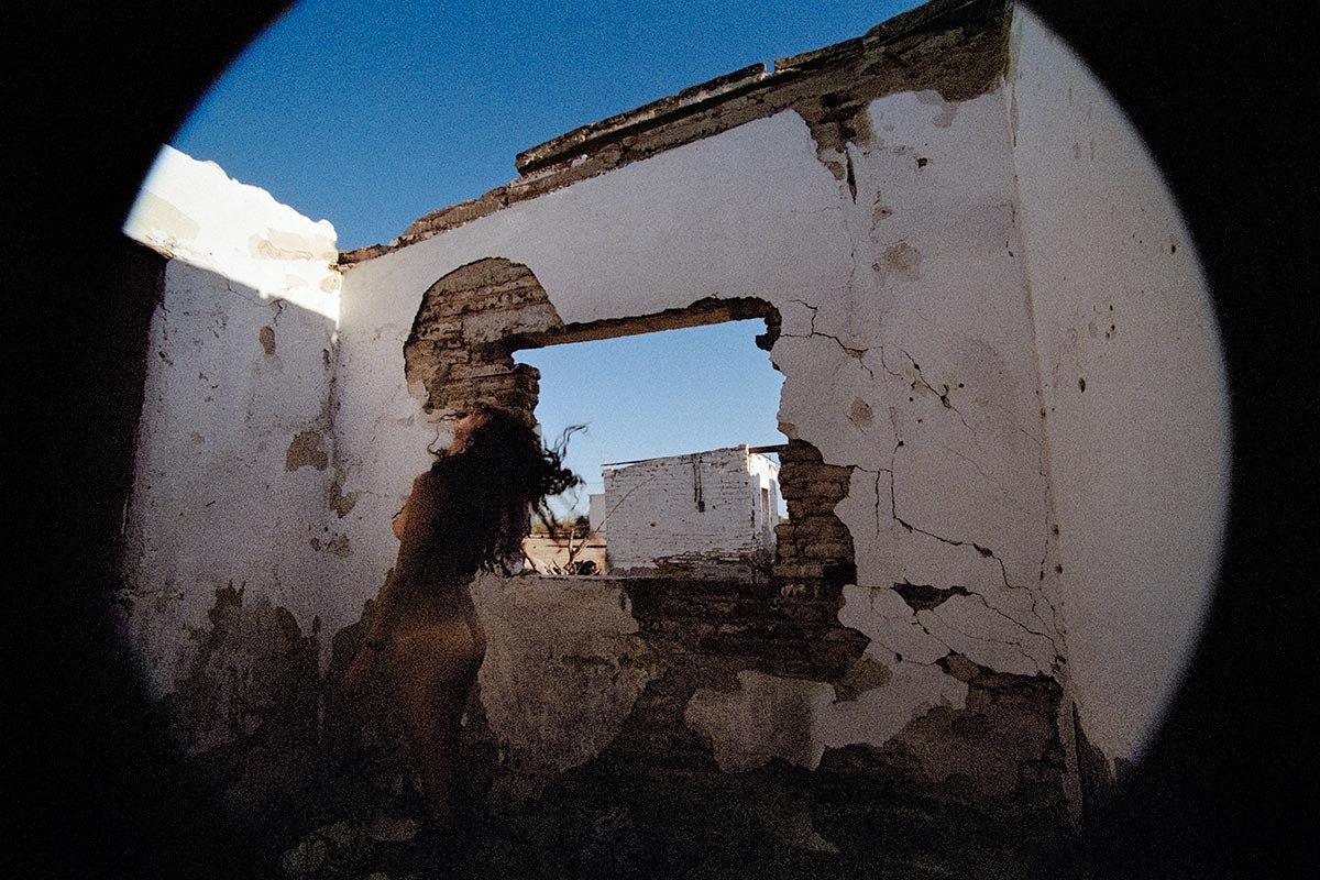 nude woman with her back partially to the camera throwing her head back in the middle of a half destroyed structure with white stucco walls and no ceiling.