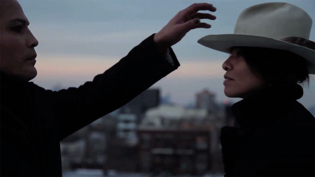 Young man and woman in profile at edges of picture. The young man reaches across as if to take a cowboy hat off of the woman's head.