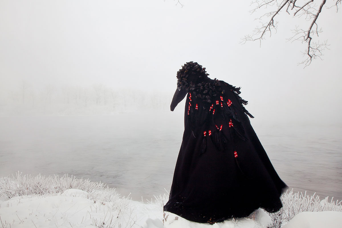 A black caped figure with a raven's head mask stands in snow with heavy mist over a lake obscuring the background.