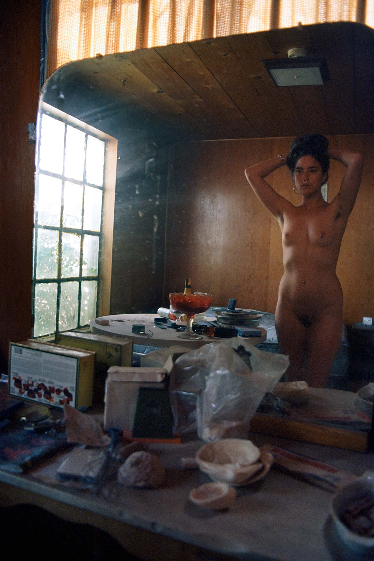 Nude woman holding her long hair gathered to the top of her head looking at herself in a mirror in a dirty derelict space