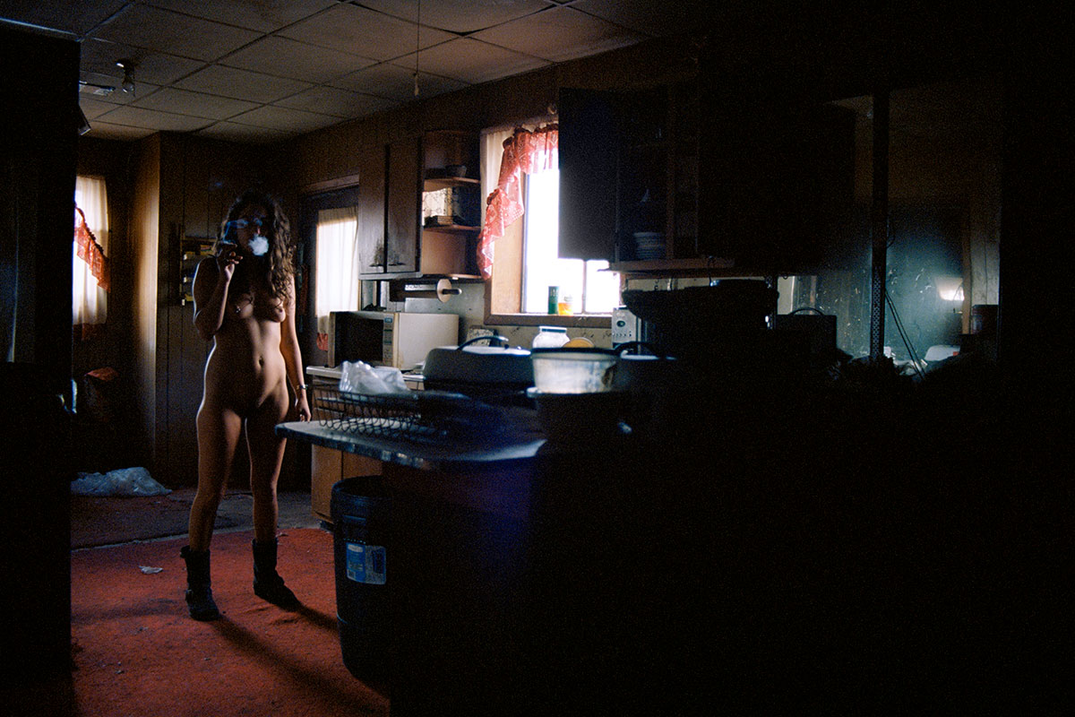 Nude woman wearing only boots smoking in a derelict kitchen interior