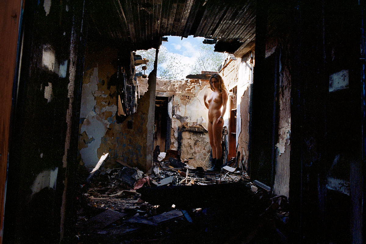 nude woman stands in a burnt out wreck of a building