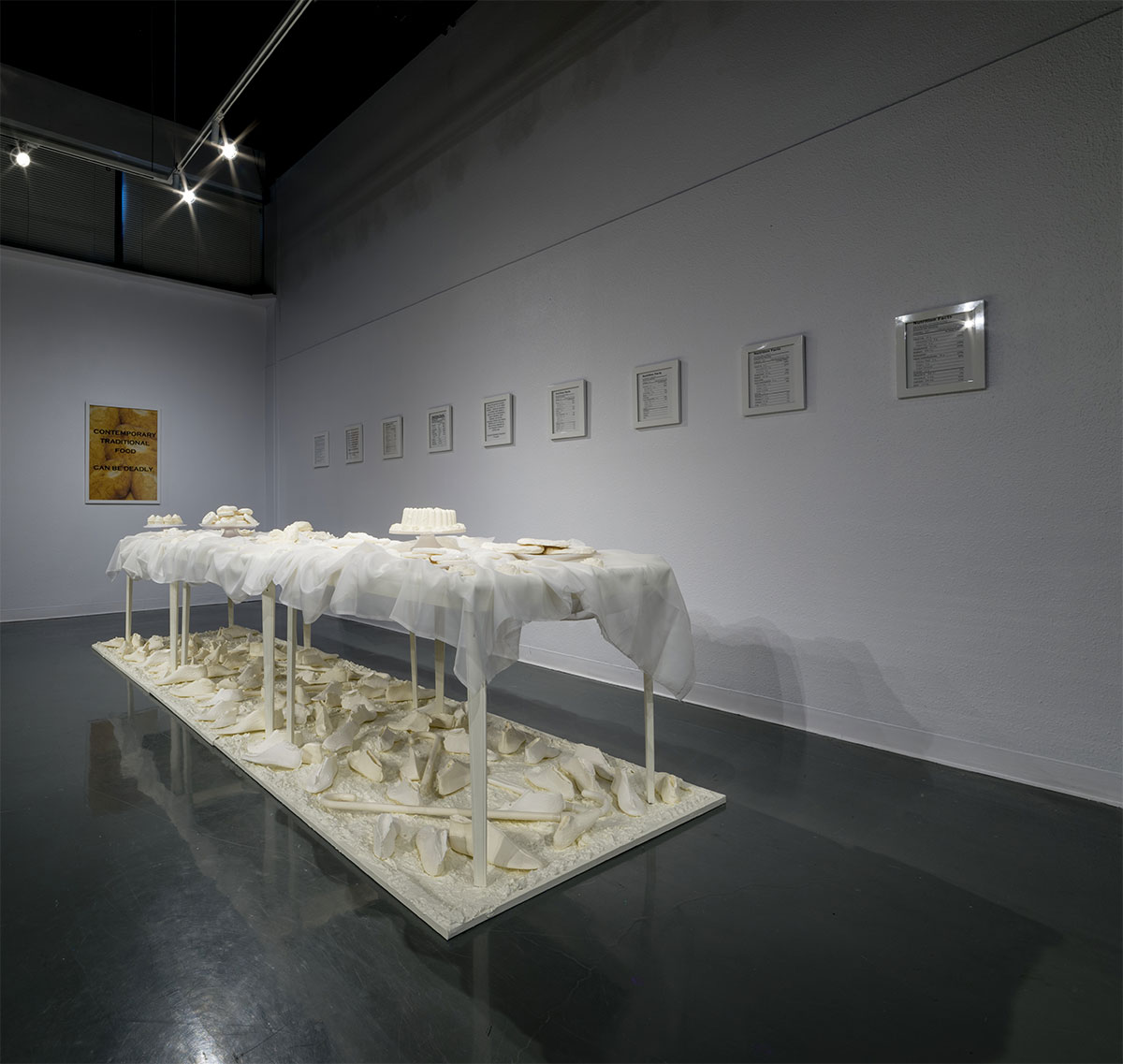Tables aligned length-wise with all-white junk food on a plinth with all-white shoe forms scattered beneath.