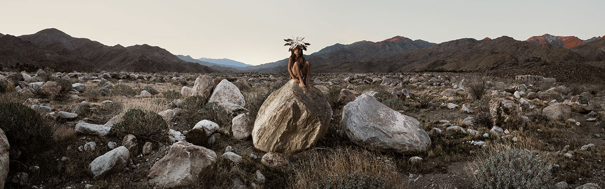 mountainous landscape in background ringing a boulder strewn valley. A young Native American child in breech cloth and feathers arrayed on the top of his head sits in the middle of the valley on a large boulder staring at the camera.